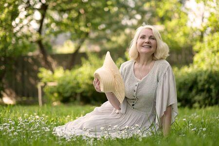 Photo pour Senior woman in dress sitting on grass at the park - image libre de droit