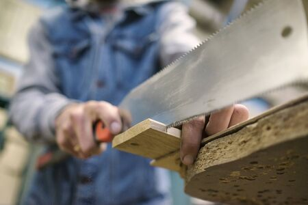 Sawing a wooden board with special japanese hand saw or hacksaw during carpentry