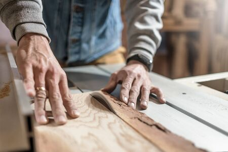 Photo pour Electric saw cutting wood board. Man working at carpentry workshop - image libre de droit