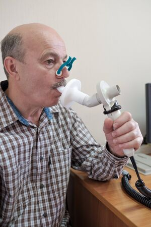 Photo pour Senior hispanic man man testing breathing function by spirometry - image libre de droit