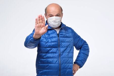 Photo for Senior man in blue jacket wearing medical mask trying to protect himself from flu gesturing stop sign. - Royalty Free Image