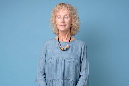 Photo pour Positive senior smiling woman with eyes closed standing meditating against blue background - image libre de droit