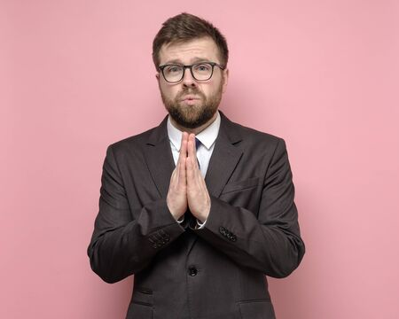 Photo for Attractive man in suit with an imploring expression on face folded palms and looks with pity. - Royalty Free Image
