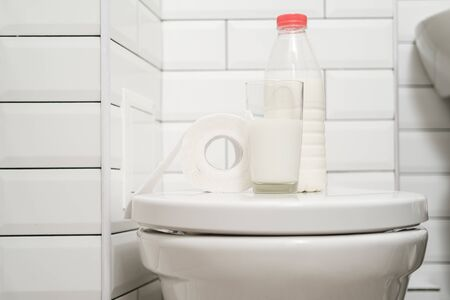 Photo pour Concept of lactose intolerance. Glass of milk, a bottle of dairy product and a roll of toilet paper are on the toilet bowl. - image libre de droit