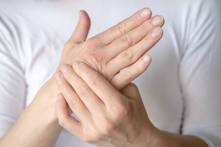 Photo pour Woman experiences pain in her hand and is massaging a sore spot against a white tee-shirt. - image libre de droit