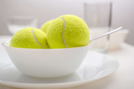 Foto per Yellow tennis balls in a bowl instead of ice cream, on the table, among the dishes. Concept of proper nutrition and sports. - Immagine Royalty Free