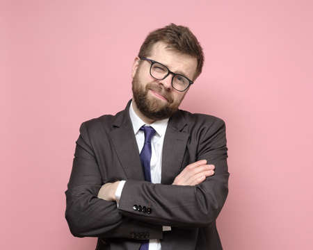 Photo for Friendly Caucasian bearded man in glasses and a suit stands with crossed arms and smiles cutely. Pink background. - Royalty Free Image