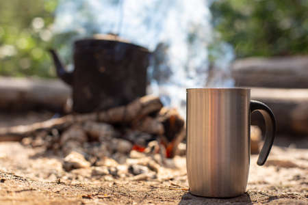 Photo pour Metal mug with a hot drink stands on the ground, against the background of a campfire with a kettle, on a hike, in the forest. - image libre de droit