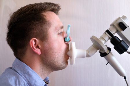 Photo pour Young man testing breathing function by spirometry - image libre de droit