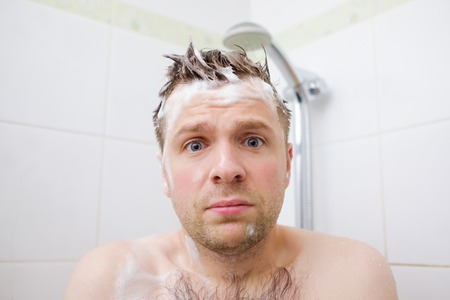Foto de Worried caucasian foamed young man after the water in the shower was turned off, looking at the camera. - Imagen libre de derechos