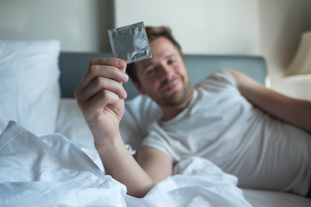 caucasian man holding condom for use it to protect and lieing in bed