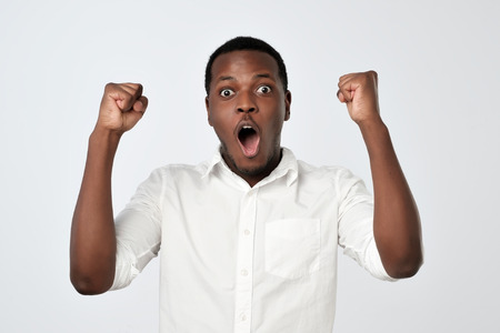 Photo pour Young african man celebrating victory over gray background - image libre de droit