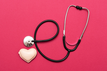 Photo pour Heart with stethoscope on red background. Flat lay view. - image libre de droit