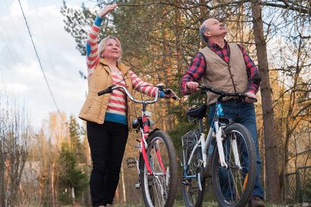 Photo pour Happy elderly senior couple cycling in park together - image libre de droit