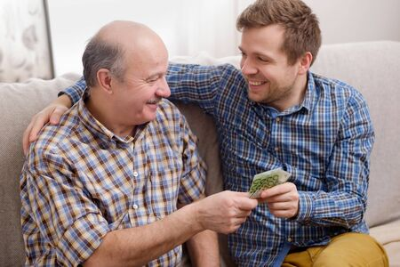 Photo for Elderly father lends money to his adult son. He helps his child deal with financial problems. - Royalty Free Image