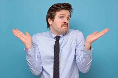 Photo pour Caucasian businessman shrugging shoulders over blue background - image libre de droit