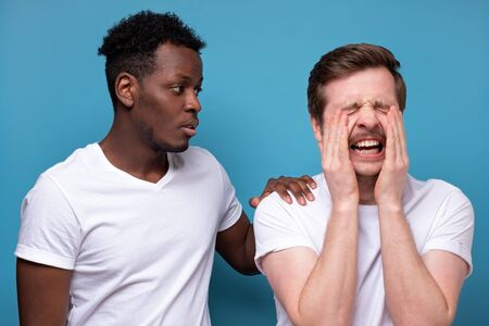 African american man calms down his colleague or friend, who has troubles, miserable facial expressions, keeps hands on his shoulders, stands closely against blue background.