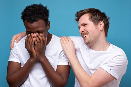 Caucasian man calms down his african american colleague or friend, who has troubles, miserable facial expressions, keeps hands on his shoulders, stands closely against blue background.