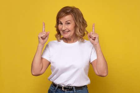 Photo pour Senior smiling woman pointing up giving advice. - image libre de droit