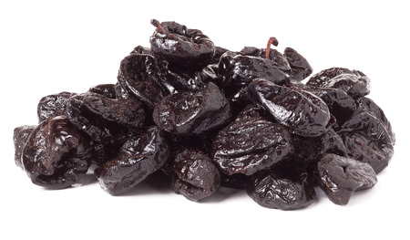 heap of dried prunes isolated on a white background closeup.