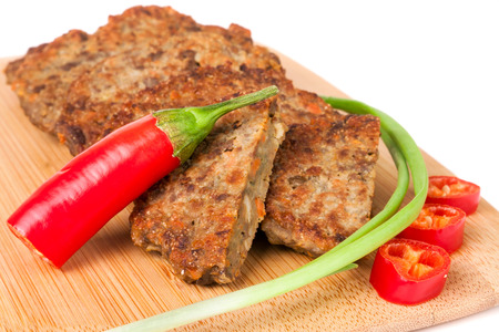 Photo for liver pancakes or cutlets with chilli and spring onions on a cutting board close-up isolated white background - Royalty Free Image