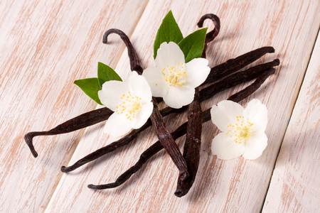 Vanilla sticks with flower and leaf on a white wooden background.