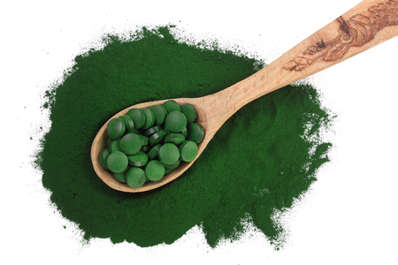 Spirulina algae powder and pills in wooden spoon isolated on white background. Top view.