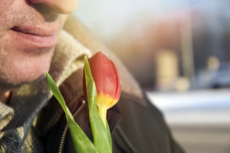 Photo pour Man hold red tulip in his hand on the blurred background of a street - image libre de droit