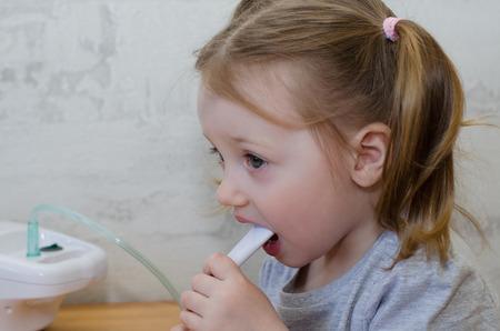 Photo pour a little girl makes inhalation at home with an inhaler - image libre de droit
