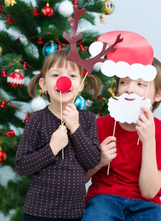 children plays with Christmas masks of Santa and deer