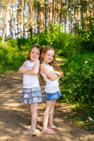 Two little girl girl friends hugging in the forest on a sunny afternoon