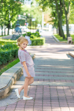 Portrait of a blonde in pink attire in a park outdoors. Vintage style