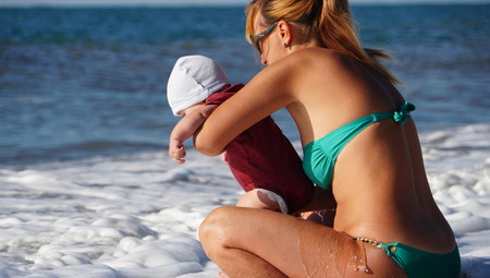 Photo pour Portrait of the woman with cute baby in the mothers hands on the beach - image libre de droit
