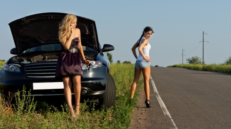 Two girls wait for the help on the road