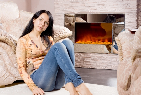 Serious attractive woman relaxing at home sitting on the floor in front of a warm winter fire resting her back against a comfortable armchair