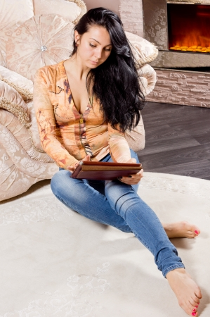 Smart casual young woman with long brunette hair relaxing sitting on the floor in front of a warm fire working on a tablet