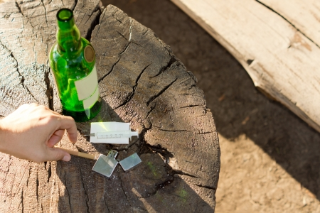 close-up of different objects, symbols of addictive habits: a syringe, a bottle of wine, a lighter and a brown cigarette