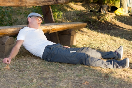 Heroin user passed out on the ground with his head on a bench in the park