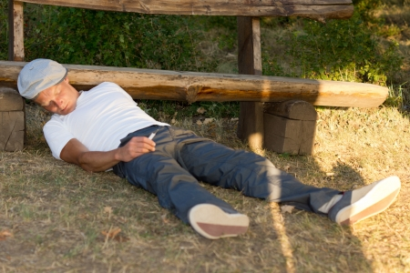 Addicted man passed out on the ground in the park because of an overdose