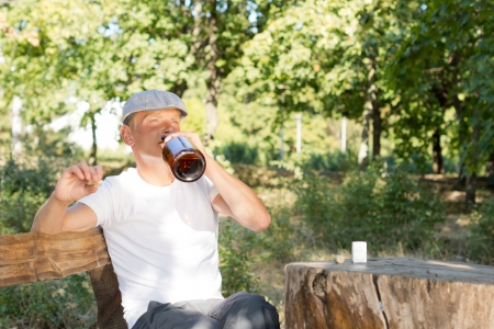 Man with a drinking problem sitting alone drinking from a bottle of liquor and smoking a joint or cigarette at a rustic table in a park