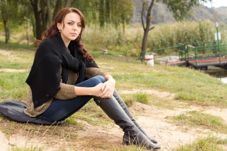 Thoughtful lonely young woman in trendy boots and jeans sitting on a cushion on the ground in a park cradling her knees in her arms as she stares at the camera