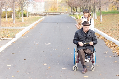 Female carer helping a disabled elderly man in a wheelchair pushing him along the street and carrying a bag of groceries from the supermarket