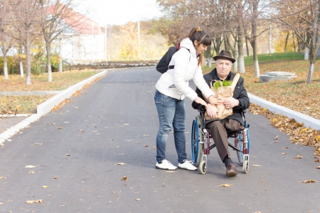 Daughter handing an elderly disabled man in a wheelchair a bag of groceries as she prepares to push him along the street after taking him shopping