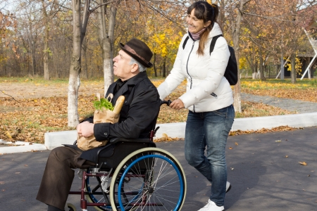 Happy woman helping a disabled elderly man as she pushes his wheelchair along a road on their return from doing the grocery shopping