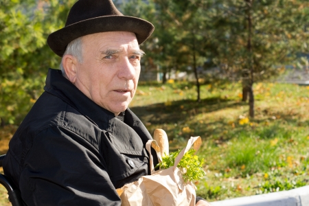Elderly gentleman in a wheelchair with his groceries in a brown paper packet on his lap as he returns from the shops, close up portrait