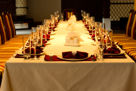 View down the length of a long formal dinner table with red accented place settings with linen, elegant glassware, silverware and centerpieces for a special event