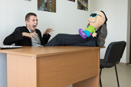 Young Male Office Worker Playing with Stuffed Toy, with Feet on the Table, Showing Monster Face at Office.