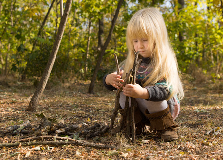 Cute pretty little girl with long blond hair crouching down on the ground in woodland building a wigwam from twigs and branchesの写真素材