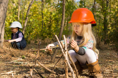 Cute little girl building a wooden tepee squatting on the ground in the woods in her hardhat while a young boy works in the background