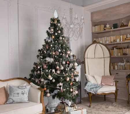 Decorated Christmas tree in an upmarket living room interior with classic vintage furniture